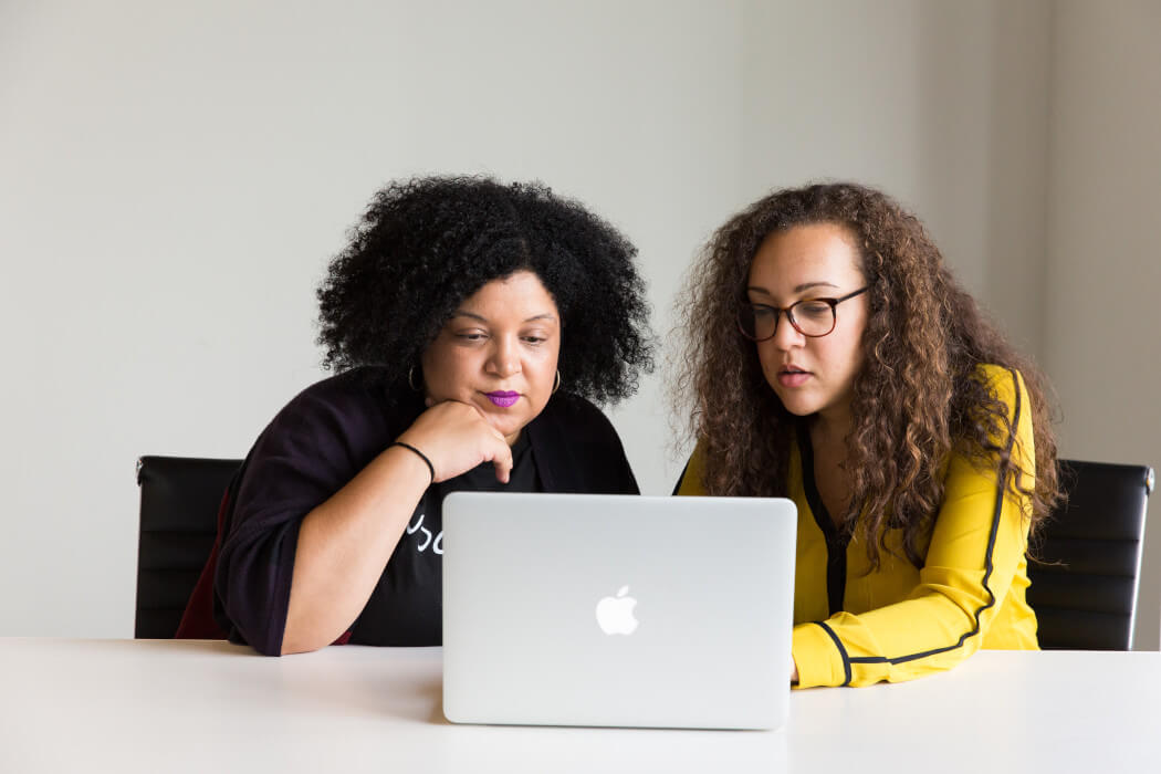 Two Black women using a laptop together