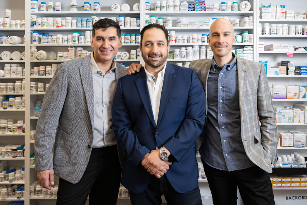 Mednow's three co-founders standing in front of pharmacy wall