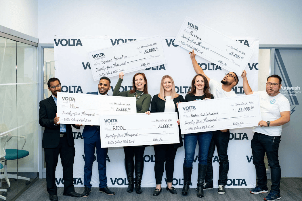 Volta pitch competition winners holding big $25,000 cheques