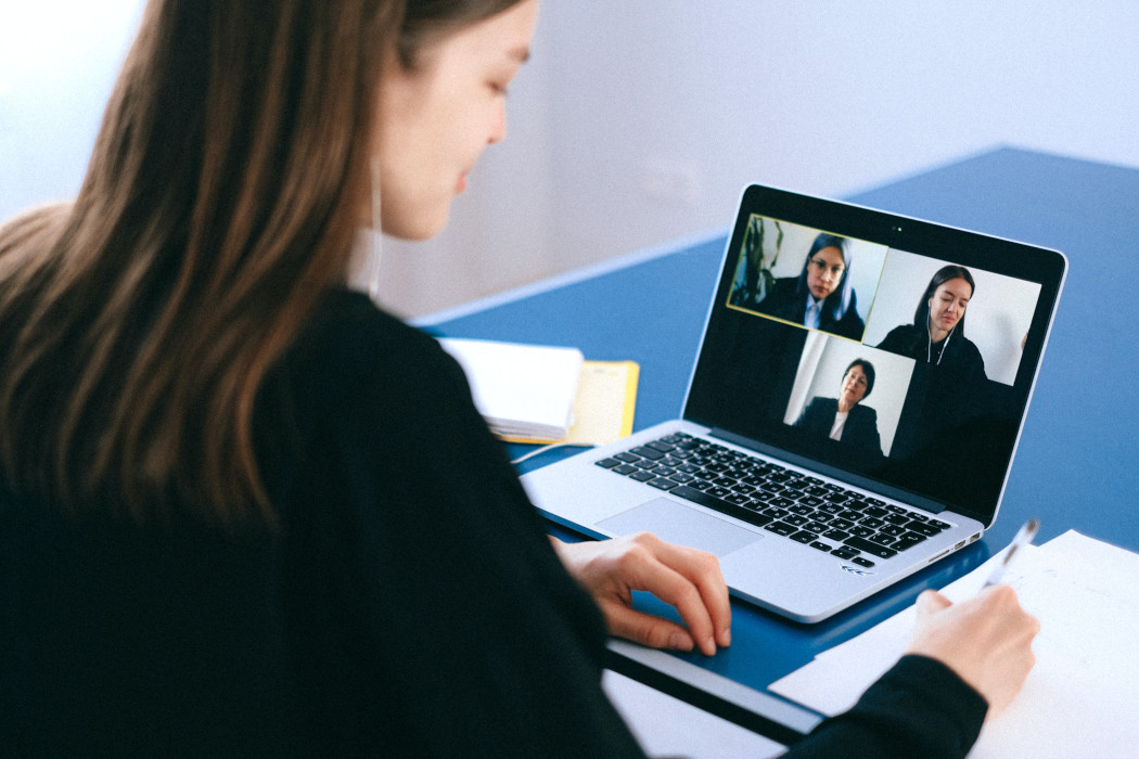 Woman dressed professionally on Zoom call taking notes