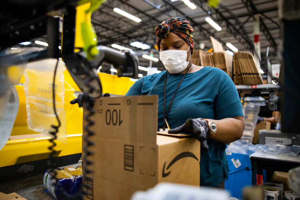 Amazon worker in fulfillment centre packing box