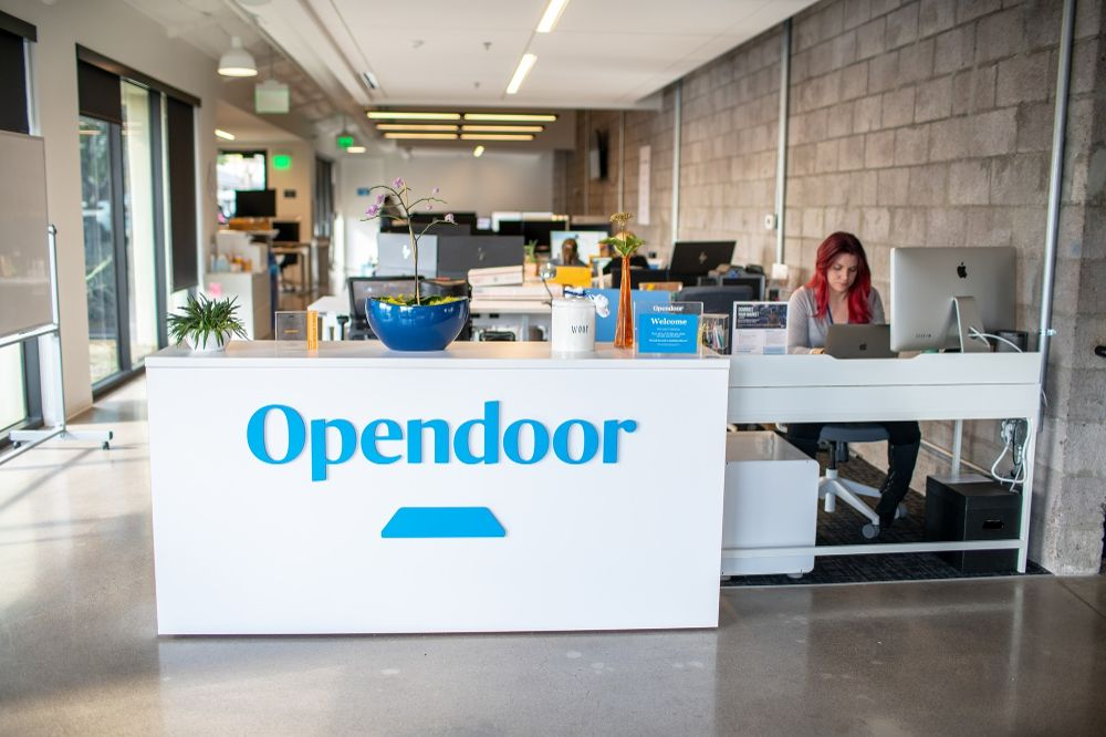 A white desk with Opendoor in blue desk at the front