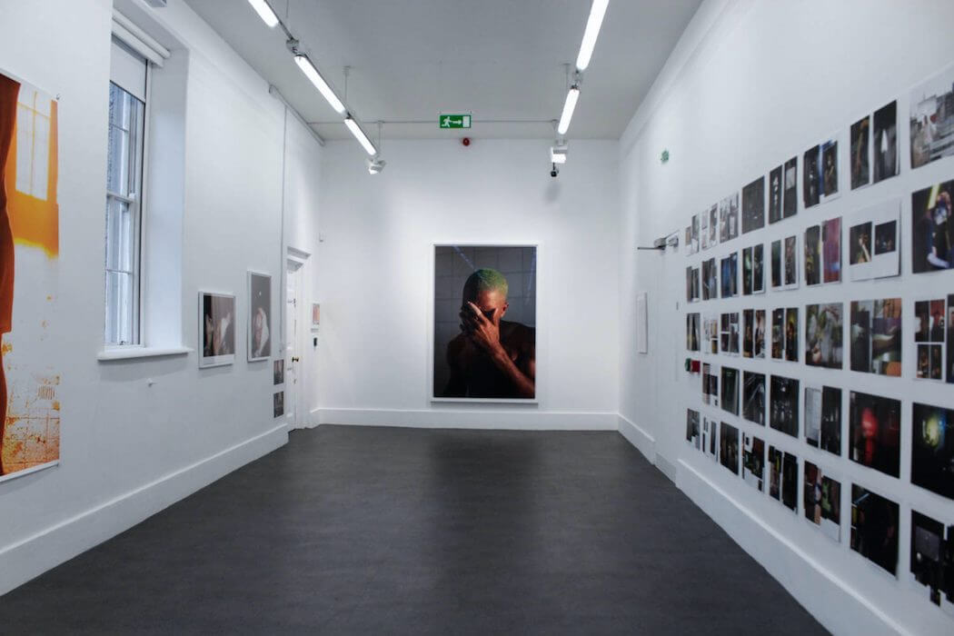 A room with white walls decorated with printed pictures. A photo of Frank Ocean is displayed in the center wall.