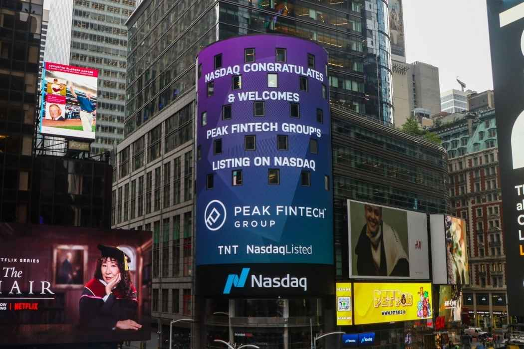 A billboard congratulating Peak Fintech Group on being listed on NASDAQ